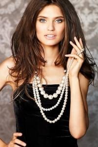 девушка в черном платье с жемчужным ожерельем